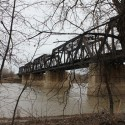 An old truss bridge is seen through dead branches