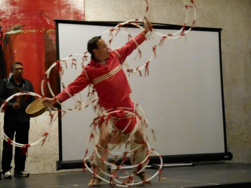 Burton Bird, dancing, making an animal shape out of white hoops with red ribbons on them