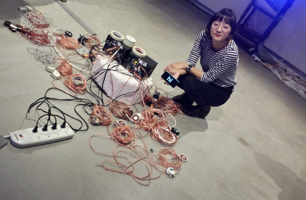 "Christine Sun Kim with her sound equipment, holding up a cell phone that says ""hi""."
