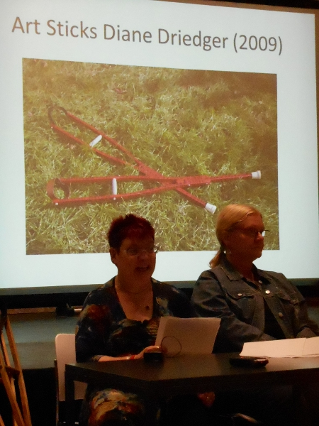 Nancy Hansen and Diane Driedger sit at a table, Nancy is lecturing, with an overhead slide of red fashion crutches behind them