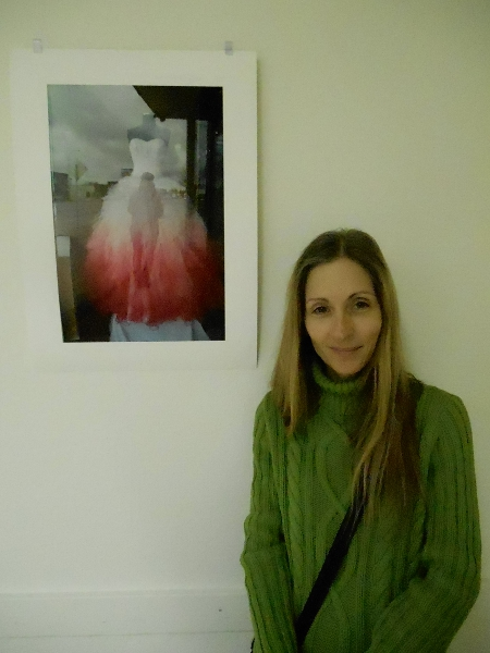 "Marie LeBlanc stands beside her photograph ""Red Dress"""