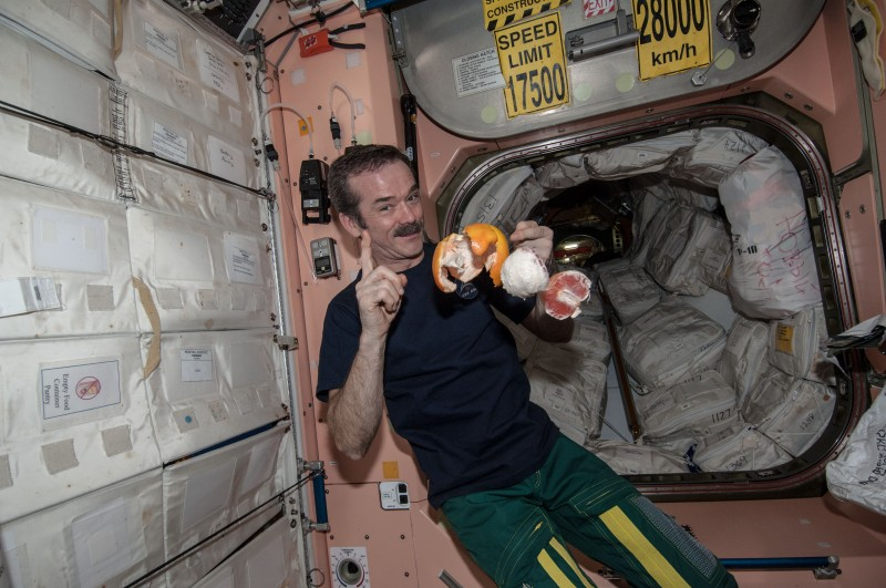 Canadian astronaut Chris Hadfield demonstrates peeling an orange in space