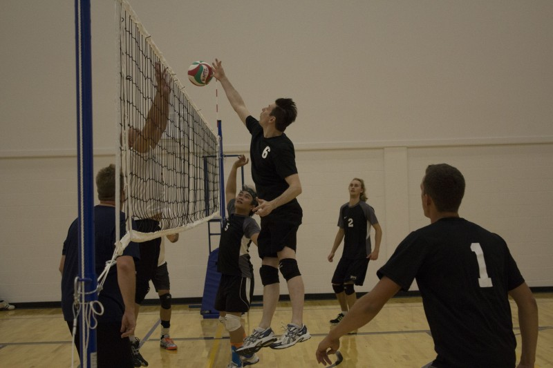 Mike Law delivers a spike on the volleyball court.
