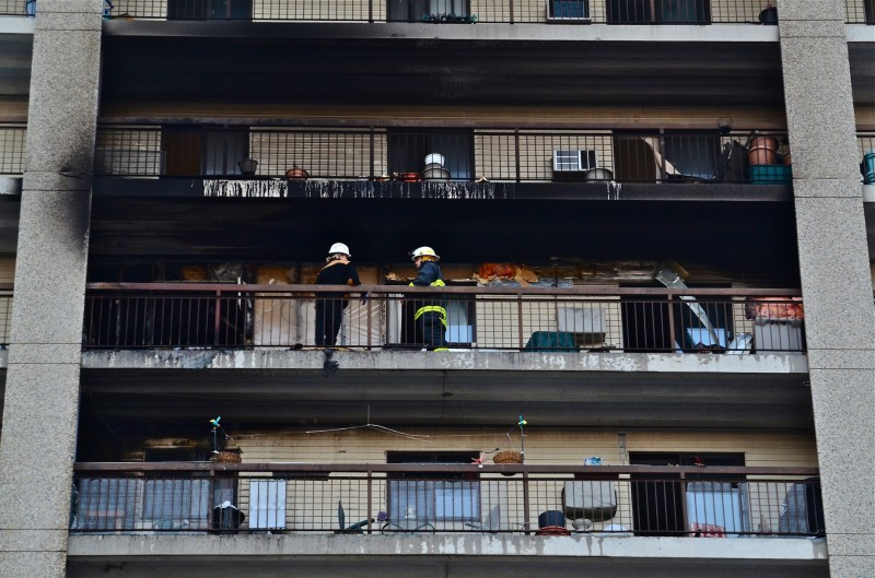 Firefighters on the 8th floor balcony below where the fire started