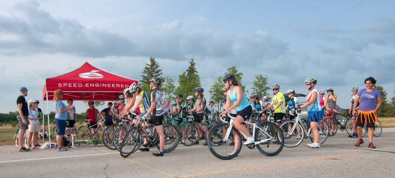 A group of road racers gets addressed by Kim Mitchell (blue, standing)
