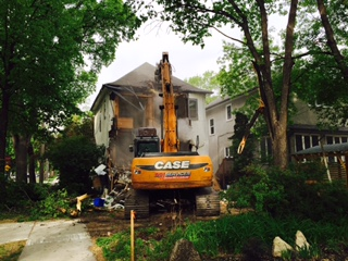 Backhoe operator demolishes house on Lilac Street, without a safety fence in place. PHOTO: Marnie Feeleus