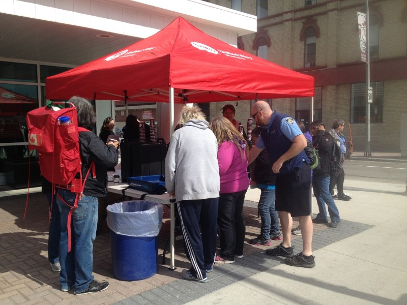 United Way staff members handing out free coffee and cookies outside their Main Street office.