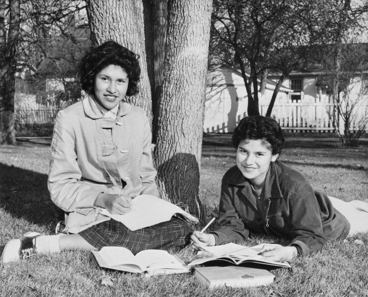 Adeline Raciette and Emily Bone study on the lawn of the Assiniboia Indian Residential School, Winnipeg, Manitoba, ca. 1958
