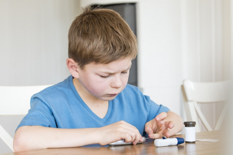 Young boy measuring blood sugar.