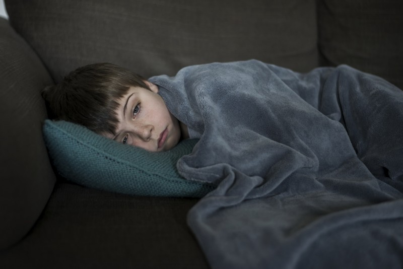 Boy sick with flu laying on the sofa.