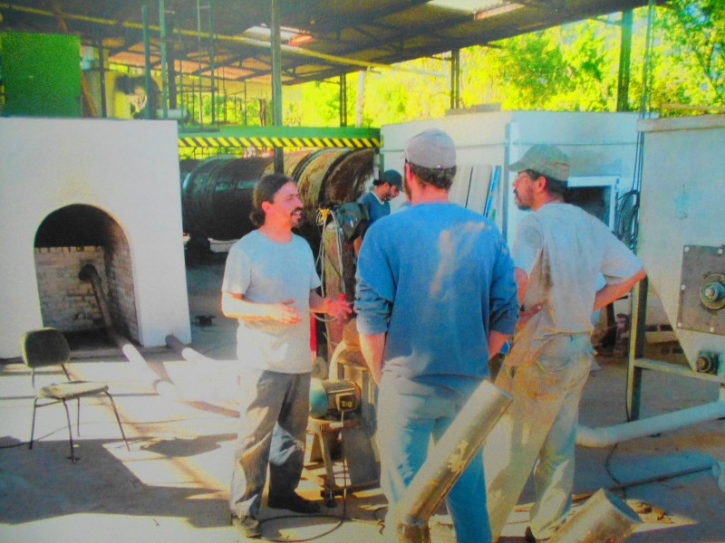 Community members in Brazil working with drying machine in the background.