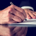 Closeup of male hand signing mortgage or other important legal or business document.