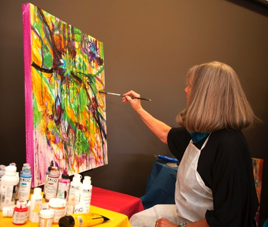 Genevie Henderson, artist, donates a painting she completes on stage.