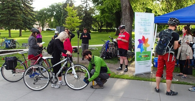 Osborne Bridge commuter stop: Eric Gosselin of Coop Vélo-Cité gives a bike a little love, while Commuter Challenge riders enjoy Tall Grass cinnamon buns (still warm) and coffee. /GREG PETZOLD