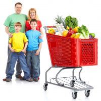 Happy family with a shopping cart. Isolated over white background.