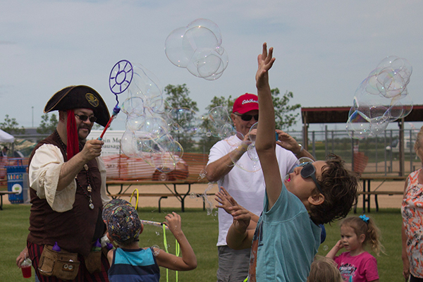 A man dressed as a pirate blows bubbles with a machine while kids jump up to pop them