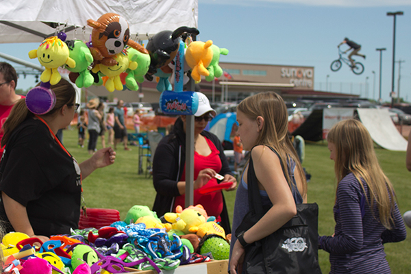 A woman looks at toys at a prize booth while a man on bike does a stunt trick in the background