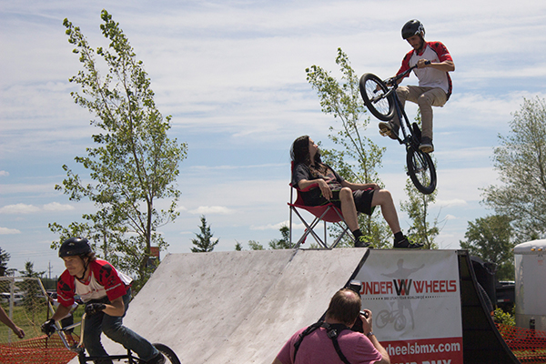 a man on a bike jumps over man seated in a chair
