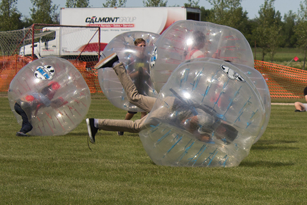 Children in large protective bubbles roll around on the ground