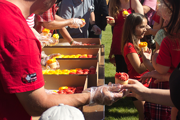 people hand out colourful cupcakes