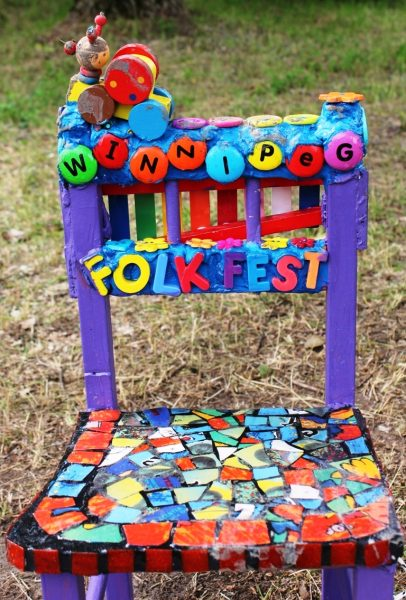 "Art at Folkfest: ""We are all a mosaic of love, light and music."" Mosaic designed table, chairs and guitar glow in the shade. /GREG PETZOLD"