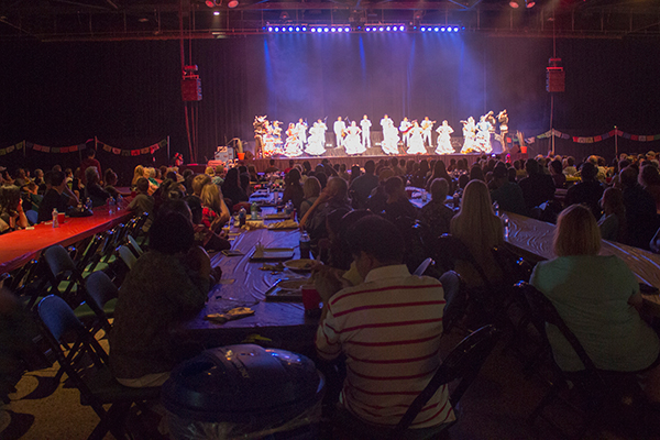 many people seated at table watch a performance on stage