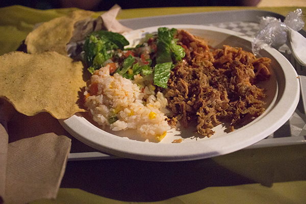 a plate of food with shredded meat, rice, salad, and taco shells