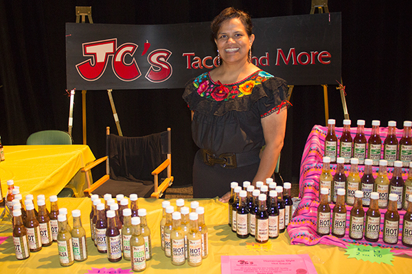 a woman stands behind a table with hot sauce for sale