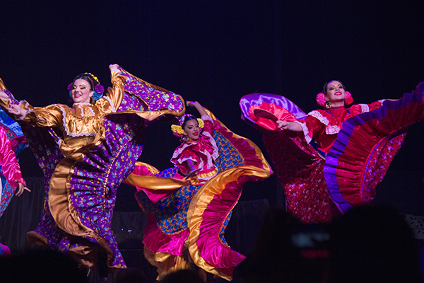 three women dance in vibrant costumes