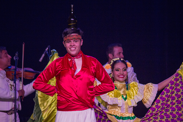 a male dancer balances a tequila bottle on his head