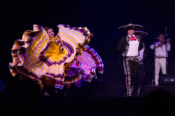 a female dancer swirls her shirts next to a male dancer in a sombrero, with a musican in the background