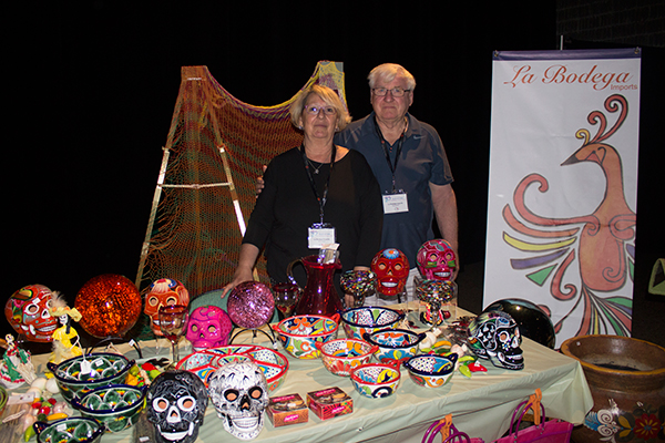 a man and woman stand in front of pottery and decorative items for sale