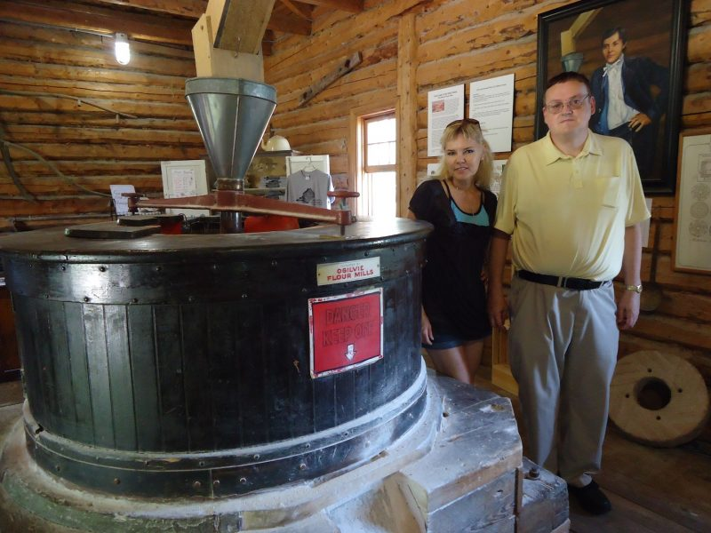 Reporter Shirley Kowalchuk and historian Jim Smith at Old Grants Mill with Cuthbert Grant portrait in background.