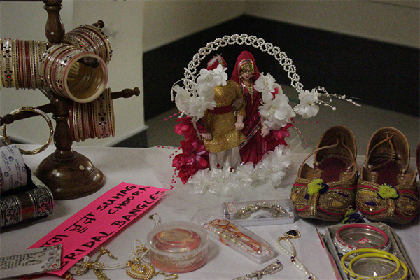 bracelets and other jewellery on a table with bride and groom dolls