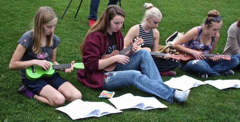 Violet, Abby, Casie and Rosie getting comfortable on the grass with strumming along