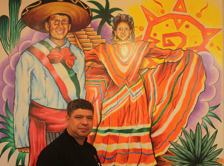 Owner Marvin Dubon in front of wall mural depicting his children Josue and Corina in traditional attire