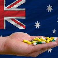 holding pills in hand in front of australia national flag