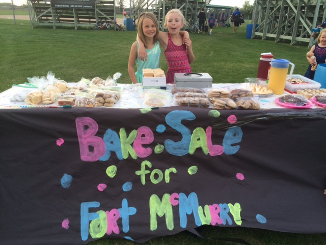 Sydney, 7 going on 17 (on left) and her friend Rhea recently organized this bake sale that raised $221 for Fort McMurray. Have faith. . .the world is safe in their hands! PHOTO by Tammy Boughton