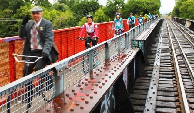 Don't rain on my parade: on the 10th anniversary of Bike to Work Day cyclists roll across the Omand's Creek railway bridge heading downtown. PHOTO by Greg Petzold