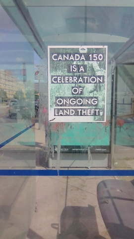 Sign of the times: poster on bus shelter in Winnipeg prompts discussion about country's anniversary. PHOTO by Anne Hawe
